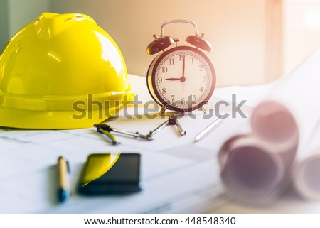 Morning time it's nine o'clock already, A retro clock showing 9:00 am on the desk of engineer designer and architect in an office with equipment and drawing paper for working plan. - stock photo