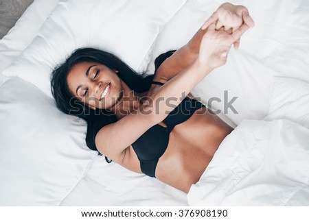 Morning vibes. Top view of beautiful young African woman in black lingerie lying in bed and stretching her arms - stock photo