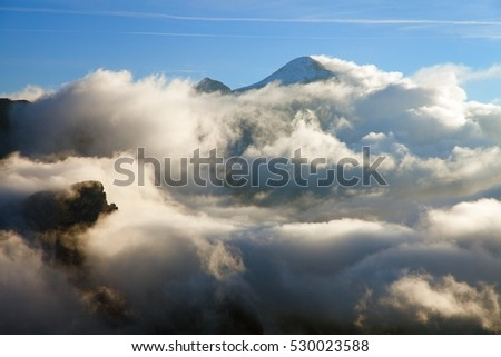 Morning view from Col di Lana to Gruppo Tofana or Le Tofane gruppe in the middle clouds and fog, South Tirol, Alps Dolomites mountains, Italy