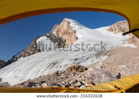 Morning View from Yellow Tent Glacier and High Mountain Peak Taken throw Window Entrance Door of Alpine Tent Blue Sky Rocky Moraine - stock photo