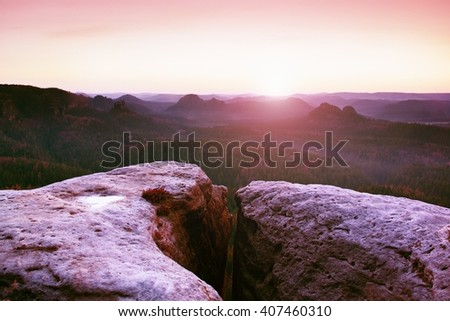Morning view over sandstone cliff into forest valley, daybreak Sun at horizon. Hills increased from foggy background - stock photo