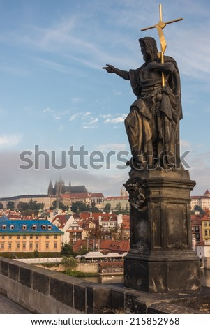 Morning view to the lesser town and the Prague Castle from Charles Bridge having a statue of John the Baptist in the foreground - stock photo