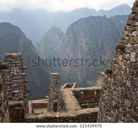 Morning views of Machu Picchu showing stone walls of buildings above valley
