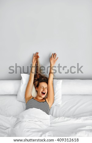 Morning Wake Up. Attractive Smiling Young Woman Waking Up Fully Rested On White Bedding. Beautiful Healthy Model Girl Stretching Her Arms While Lying On Bed And Relaxing At Home. - stock photo