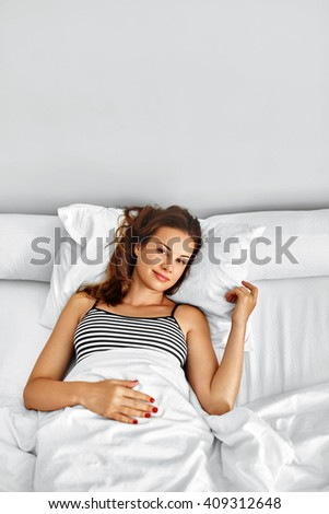Morning Wake Up. Beautiful Smiling Woman Lying Fully Rested After Waking Up On Bed In Her Bedroom. Happy Girl Had Healthy Sleep On White Bedding. Female Relaxing At Home. - stock photo