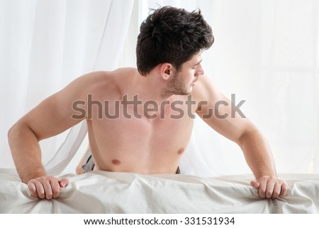 Morning Wake up. Stripped handsome man lying in bed with a naked torso. Young boy lying in bed with his pants unbuttoned and looking out the window