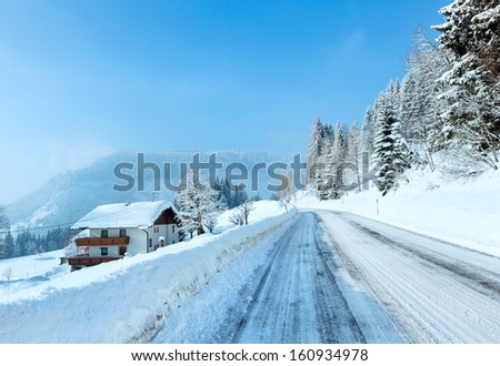 Morning winter misty rural view with alpine road and house on the roadside. - stock photo
