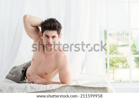 Morning with a young handsome man. Stripped handsome man lying in bed with a naked torso. Young boy lying in bed with his pants unbuttoned. - stock photo