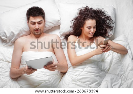 Morning with gadgets. Overhead of beautiful young couple lying on the bed using tablet computer and smartphone, Top view.