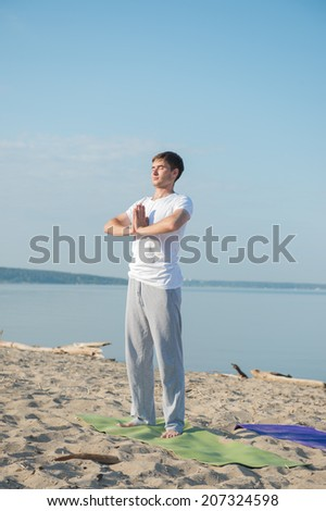 Morning Yoga Meditation at the Beach by man - stock photo