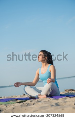 Morning Yoga Meditation at the Beach by woman - stock photo