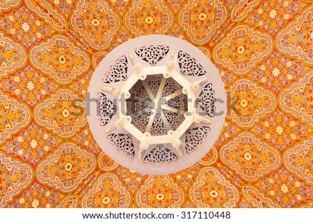 Moroccan ceiling lamp with traditional design on the colorful ceiling - stock photo