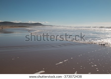 Moroccan coast of the Atlantic Ocean Late afternoon on the sandy beach of the Atlantic Ocean in Morocco. Waves of a tide. Mountain in the background. Blue sky with some clouds. - stock photo