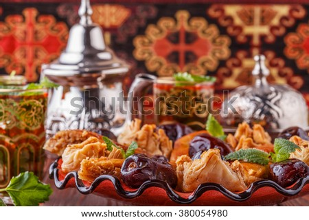 Moroccan mint tea in the traditional glasses with sweets, selective focus. - stock photo