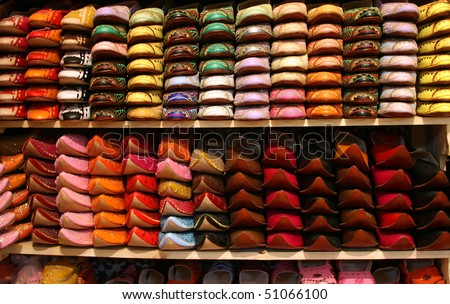 Moroccan slippers lined up on a shoe rack in a shop