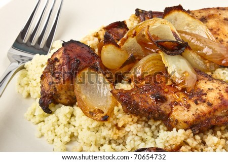 Moroccan Spiced Chicken with couscous and onions isolated on white.