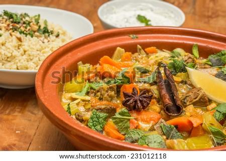 Moroccan tagine dish with chick peas, lamb, carrots, celery, lemon, onion, cinnamon, star anise, bulgur - stock photo