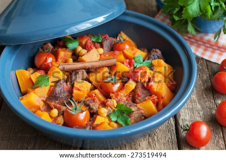 Moroccan Tagine with beef, chickpeas,  pumpkin and cherry tomatoes on a wooden table. Selective focus - stock photo