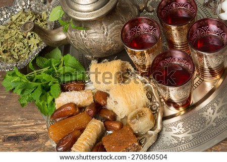 Moroccan tea tray with mint leaves and ramadan cookies and dates - stock photo