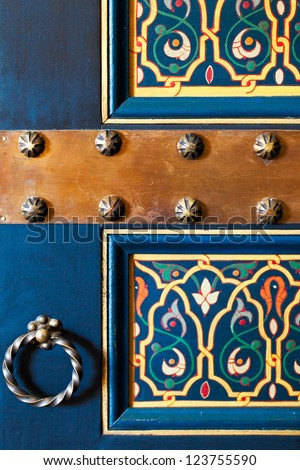 Moroccan wooden painted door.  Close up detail of floral design on a deep blue background, bronze knocker and metal nail heads. Location: Marrakech, Morocco - stock photo
