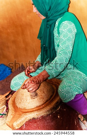 MOROCCO, ATLAS MOUNTAINS-OCTOBER 06, 2014: Moroccan Argan oil production- Female worker grinding Argan nuts - stock photo