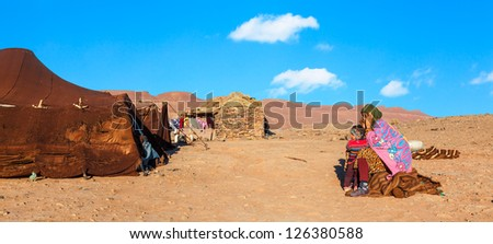 MOROCCO-DEC 28: Unidentified nomad mother and child in the Sahara desert in Morocco on Dec. 28, 2012. Nomadic Berbers traditionally camp here in the Maider region to graze their herds. - stock photo