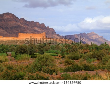 Morocco, Draa Valley, Zagora, Medieval Kasbah built in adobe with mountains in the background and fertile river valley with date palms in the foreground.  - stock photo