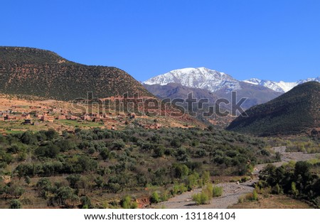 Morocco, High Atlas Mountains, Snow covered peaks of Toubkal National Park and stone and adobe built village above the river valley near Ansi. - stock photo