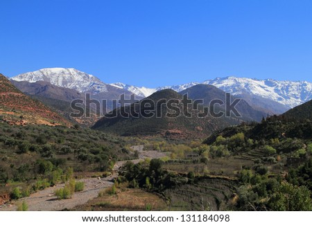 Morocco, High Atlas Mountains, Snow covered peaks of Toubkal National Park and the river valley near Ansi. - stock photo