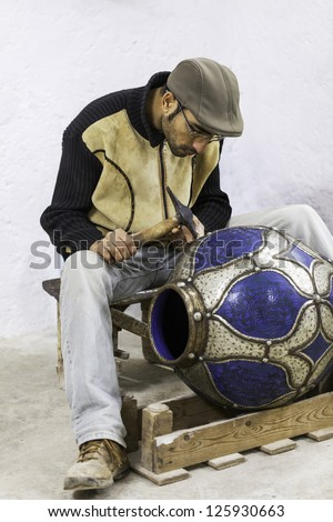 MOROCCO-JAN.3: A ceramic artist works on a large vase with metal accents in Fez, Morocco on Jan. 3, 2013. Fez has been a center of fine pottery production for thousands of years.