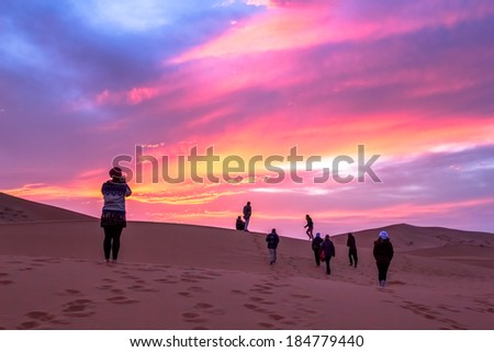MOROCCO - January 16, 2014: A group of travelers rush to take pictures of the sunset over the dunes in the Sahara desert.  - stock photo