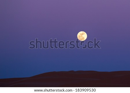 MOROCCO - JANUARY 10, 2014: Full moon over the sahara desert dunes - stock photo
