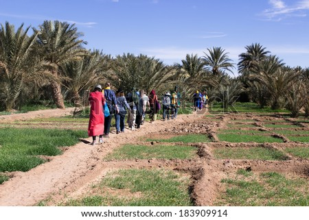 MOROCCO - JANUARY 10, 2014: Travelers walk on the outskirts of the Sahara desert - stock photo