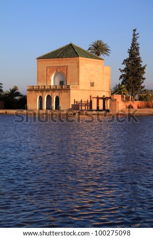 Morocco Marrakesh Menara Pavilion reflected on lake in late afternoon sunshine - stock photo