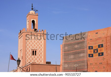 Morocco Marrakesh Mosque minaret and typical Berber rugs hanging in the sunshine in Jemaa El Fna Square - stock photo