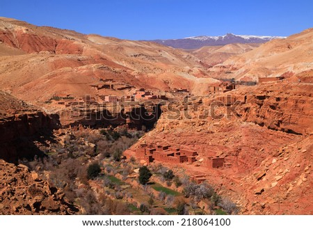 Morocco, Marrakesh to Ouarzazate road, High Atlas Mountains, an isolated typical Berber village built in adobe, Springtime. Snow capped mountains in the background. - stock photo