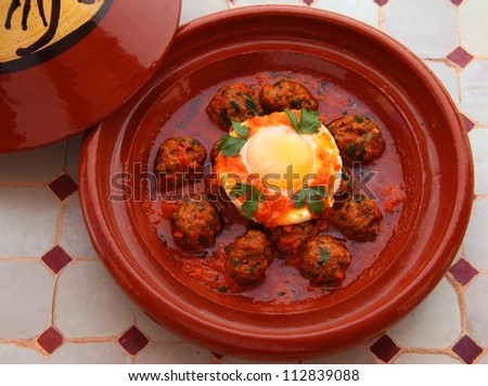Morocco Tajine of Kafta - Typical Moroccan and Lebanese dish of meatballs in a tomato sauce with paprika cumin and garlic, with an egg poached in the sauce - cooked in a clay 'tajine' dish - stock photo