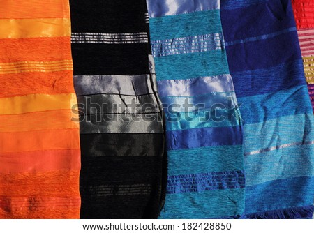 Morocco, Typical colourful  hand crafted silk cloth covers on display in a Medina souk. - stock photo