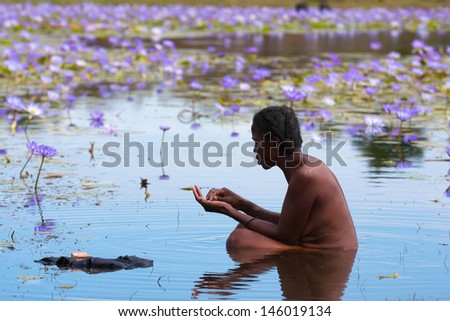 MORONDAVA, MADAGASCAR, MAY 11: Unknown Malagasy woman bathes in a pond with lilies near the Avenue of Baobabs, Morondava, Madgaskar, may 11, 2009 - stock photo