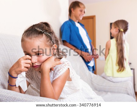 Morose little girl is jealous sister of stepbrother indoors - stock photo
