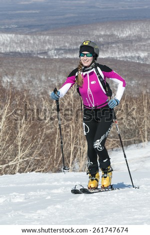 MOROZNAYA MOUNT, KAMCHATKA, RUSSIA - APRIL 25, 2014: Ski mountaineer Sorvinkova Tatiana climb on skis on mountain. Vertical race ski mountaineering Asian, ISMF, Russian and Kamchatka Championship. - stock photo