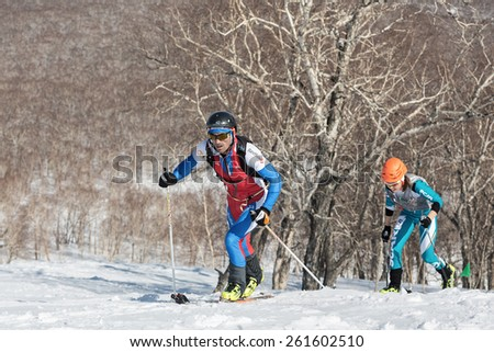 MOROZNAYA MOUNT, KAMCHATKA, RUSSIA - APRIL 25, 2014: Two ski mountaineer climb on skis on mountain. Vertical race ski mountaineering Asian, ISMF, Russian, Kamchatka Championship. - stock photo
