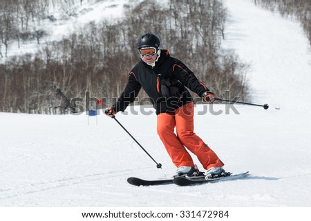 MOROZNAYA MOUNTAIN, YELIZOVO, KAMCHATKA, RUSSIA - APRIL 17, 2015: Young woman skier coming down the ski from mountain on a sunny day. Russia Far East, Kamchatka Peninsula. - stock photo