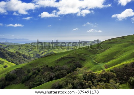 Morro Rock, Morro Bay, Montana de Oro & rural coastal hills / mountains, blue sky, white clouds, & green grass, as seen from Highway 46 on the Big Sur coast, California Central Coast, near Cambria CA. - stock photo