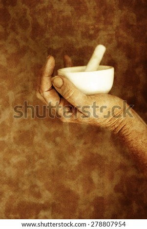 Mortar and Pestle in hands - stock photo