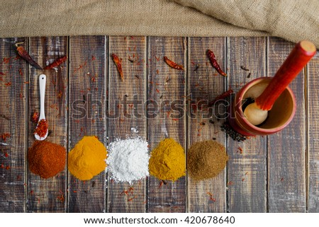 Mortar and pestle near white spoon with different of spices on the wooden table, top view.  Heap of different dry spices on a wooden background. - stock photo