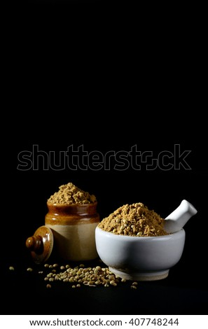 mortar and pestle with Coriander Powder and seeds on black background. - stock photo