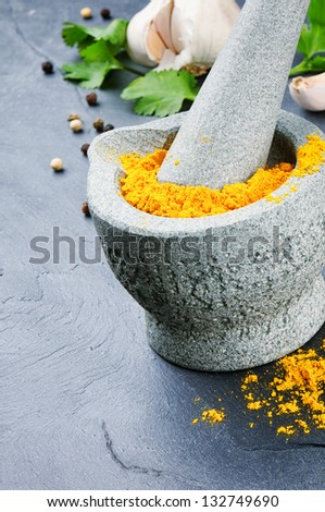Mortar and pestle with curry powder - stock photo