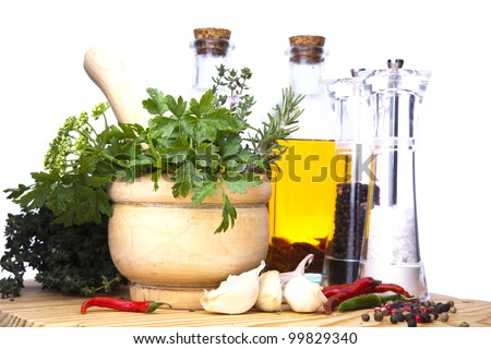 Mortar and pestle with fresh herbs, spices, virgin olive oil, salt and pepper. - stock photo