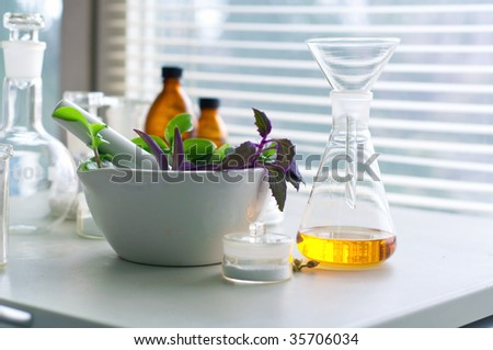 mortar and pestle with herbs with a glass of alternative fuel - stock photo